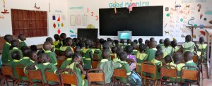 Children in the Gambia watch a DVD on their new TV, funded as a Christmas gift from TiC.